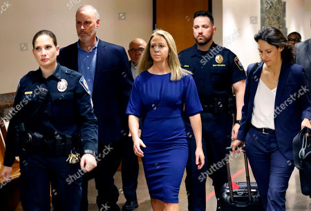 Former Dallas police officer Amber Guyger, center, arrives for the first day of her murder trial in the 204th District Court at the Frank Crowley Courts Building in Dallas, . Guyger is accused of shooting her black neighbor in his Dallas apartment
