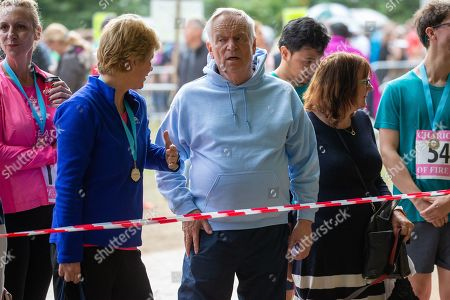 Lord Jeffrey Archer waiting for his wife Dame Mary to run past as she took part in the race in Cambridge Lord Archer had tendonitis and was struggling to walk.