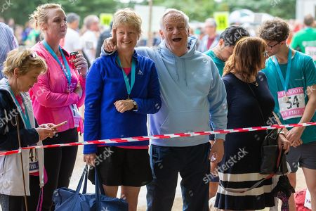 Lord Jeffrey Archer waiting for his wife Dame Mary to run past as she took part in the race in Cambridge Lord Archer had tendonitis and was struggling to walk and stand and was helped by a friend to support himself.