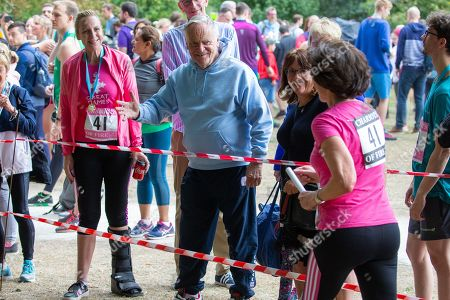 Stock Picture of Lord Jeffrey Archer watching his wife Dame Mary (pink shirt) run past as she took part in the race in Cambridge Lord Archer had tendonitis and was struggling to walk.