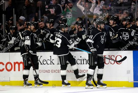 Los Angeles Kings' Dustin Brown (23) celebrates his goal with teammates on the bench during the third period of a preseason NHL hockey game against the Anaheim Ducks, in Los Angeles