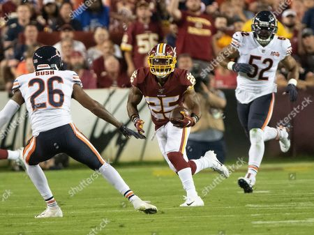 Washington Redskins running back Chris Thompson (25) carries the ball in the first quarter against the Chicago Bears. Defending on the play are Chicago Bears defensive back Deon Bush (26) and outside linebacker Khalil Mack (52)