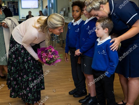Sophie Countess of Wessex receives flowers from pupils of Parkfield Primary School as she leaves the hospital after unveiling the new MRI Scanner