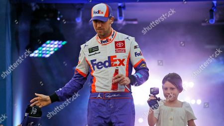 Stock Photo of Denny Hamlin, Taylor James Hamlin. Denny Hamlin and his daughter, Taylor James, greet fans during driver introductions for the NASCAR Monster Energy Cup series auto race at Richmond Raceway in Richmond, Va