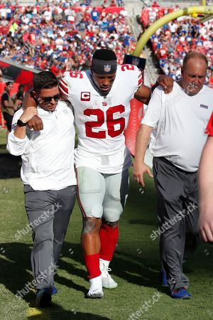 Stock Photo of New York Giants running back Saquon Barkley (26) is helped off the field after hurting his ankle against the Tampa Bay Buccaneers during an NFL football game, in Tampa, Fla. The Giants won the game 32-31