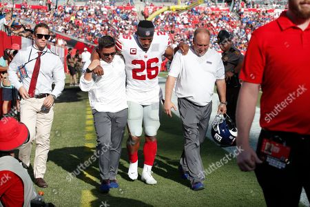Stock Image of New York Giants running back Saquon Barkley (26) is helped off the field after hurting his ankle against the Tampa Bay Buccaneers during an NFL football game, in Tampa, Fla. The Giants won the game 32-31