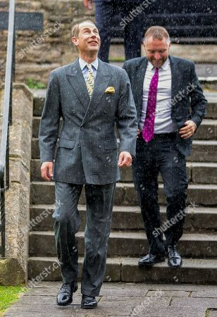 Prince Edward arrives at Wells Cathedral and is caught in a sharp shower.