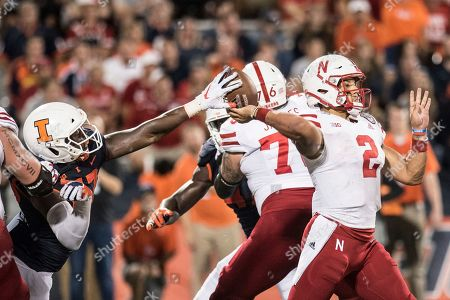 Illinois' Ayo Shogbonyo (52) gets his hand on the ball causing Nebraska quarterback Adrian Martinez (2) in the second half of a NCAA college football game between Illinois and Nebraska, Saturday, Sept.21, 2019, in Champaign, Ill