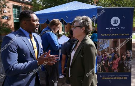 Phoenix College President Dr. Larry Johnson, left, talks with Arizona Secretary of State Katie Hobbs, right, during a voter registration drive at Phoenix College on National Voter Registration Day, in Phoenix
