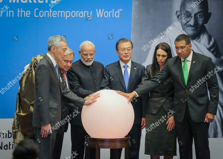 Singapore Prime Minister Lee Hsien Loong, from left to right, Bangladesh Prime Minister Sheikh Hasina, United Nations Secretary-General Antonio Guterres, India's Prime Minister Narendra Modi, South Korea President Moon Jae-in, New Zealand Prime Minister Jacinda Ardern and Jamaica's Prime Minister Andrew Holness place hands on a light ball symbolizing earth for a special event commemorating the 150th anniversary of Mahatma Gandhi, during the United Nations General Assembly, at U.N. headquarters