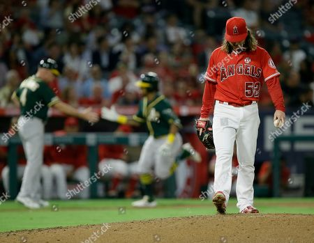 Oakland Athletics third base coach Matt Williams, left congratulates designated hitter Khris Davis for Davis' two-run home run, as Los Angeles Angels starting pitcher Dillon Peters kicks the mound during the fourth inning of a baseball game in Anaheim, Calif
