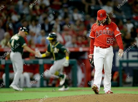 Oakland Athletics third base coach Matt Williams, left congratulates designated hitter Khris Davis for hitting a two-run home run as Los Angeles Angels starting pitcher Dillon Peters, right, kicks the mound during the fourth inning of a baseball game in Anaheim, Calif