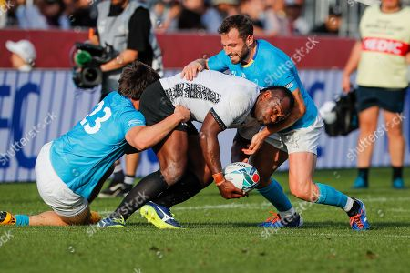 Vereniki Goneva (C) of Fiji is tackled by Tomas Inciarte (L) and Felipe Berchesi (R) of Uruguay during the Rugby World Cup match between Fiji and Uruguay in Kamaishi, Japan, 25 September 2019.