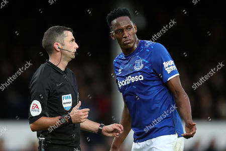 Referee Michael Oliver speaks with Yerry Mina of Everton