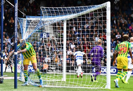 Charlie Austin of West Bromwich Albion gets caught up in the net
