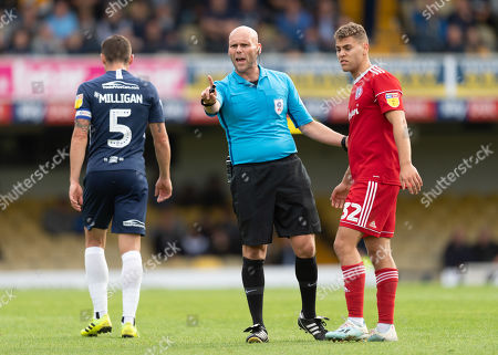 Referee Charles Breakspear warns Dion Charles of Accrington Stanley and Mark Milligan of Southend United