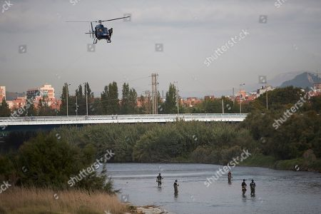 Catalan police Mossos d'Esquadra officers and firefighters take part in the search of the body of a baby who was allegedly thrown into Besos river by a 16-years old boy, the alleged baby's father, in Sant Adria, Barcelona, northeastern Spain, 25 September 2019. Policemen and firefighters try to find the body since the early hours. According to investigation sources, the boy was trying to bury the baby's body when he was surprised by several residents so he decide to throw the baby into de river. The teenager was arrested by the police.