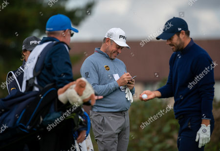 Lee Westwood marks his scorecard on the 11th green at Carnoustie, with Jamie Redknapp, right.