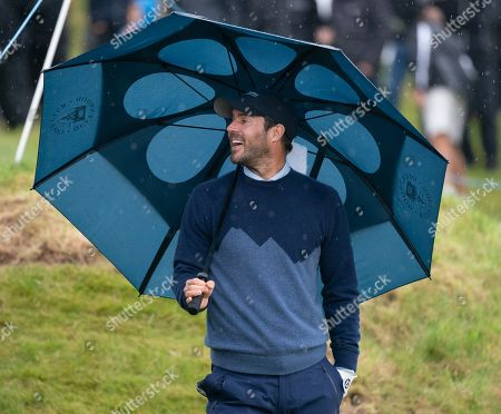 Jamie Redknapp shelters under an umbrella on the 18th fairway at Kingsbarns Golf Links, during the 2nd Round of The Alfred Dunhill Links Championship.