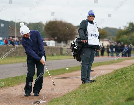 Gerry McIlroy chips rom a gravel path on to the 17th green.