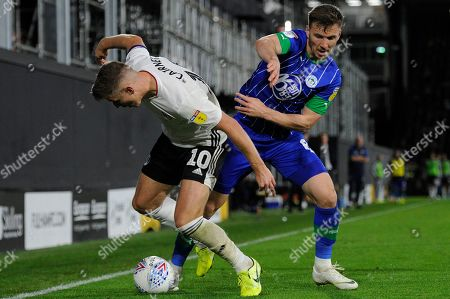 Tom Cairney of Fulham and Lee Evans of Wigan Athletic in action during the Sky Bet Championship match between Fulham and Wigan Athletic at Craven Cottage in London, UK - 27th September 2019