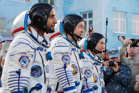 Stock Photo of From left: United Arab Emirates astronaut Hazza Almansoori, Russian cosmonaut Oleg Skripochka, and U.S. astronaut Jessica Meir, members of the main crew of the expedition to the International Space Station (ISS), report to head or Russian space agency Dmitry Rogozin prior the launch of Soyuz MS-15 space ship at the Russian leased Baikonur cosmodrome, Kazakhstan