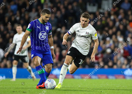 Tom Cairney of Fulham moves in the pressure Sam Morsy of  Wigan Athletic