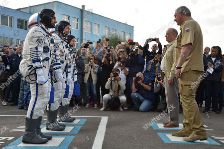 Stock Image of (L-R) Members of the main crew to the International Space Station (ISS) United Arab Emirates' astronaut Hazza Al Mansouri, Russian cosmonaut Oleg Skripochka and US astronaut Jessica Meir report to Roscosmos chief Dmitry Rogozin (R) before boarding a Soyuz rocket to the ISS, at the Russian-leased Baikonur cosmodrome in Kazakhstan, 25 September 2019. Mansouri will be the first Emirati in space.