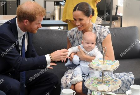 Britain's Prince Harry, The Duke of Sussex (L) and his wife Meghan, Duchess of Sussex (R) holding her son Archie, have tea with Archbishop Desmond Tutu (not pictured) and his daughter Thandeka (not pictured) at the Desmond & Leah Tutu Legacy Foundation in Cape Town, South Africa 25 September 2019. The Duke and Duchess of Sussex are on an official visit to South Africa. Founded in Cape Town in 2013, the Desmond & Leah Tutu Legacy Foundation contributes to the development of youth and leadership, facilitates discussions about social justice and common human purposes and makes the lessons of Archbishop Tutu accessible to new generations. It is located in one of Cape Town's oldest buildings and a national landmark, The Old Granary Building.