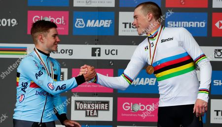Australia's Rohan Dennis, right, winner of the men's elite individual time trial event, congratulates second placed Belgium's Remco Evenepoel during the podium ceremony, at the road cycling World Championships in Harrogate, England
