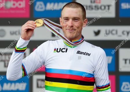 Australia's Rohan Dennis poses with his gold medal on the podium after winning the men's elite individual time trial event, at the road cycling World Championships in Harrogate, England