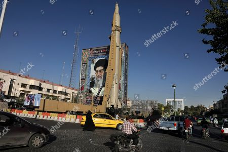 """A Shahab-3 surface-to-surface missile is on display next to a portrait of Iranian Supreme Leader Ayatollah Ali Khamenei at an exhibition by Iran's army and paramilitary Revolutionary Guard celebrating """"Sacred Defense Week"""" marking the 39th anniversary of the start of 1980-88 Iran-Iraq war, at Baharestan Sq. in downtown Tehran, Iran, . Iran's defense minister Wednesday rejected the idea of a deal with world powers over the country's missile program"""
