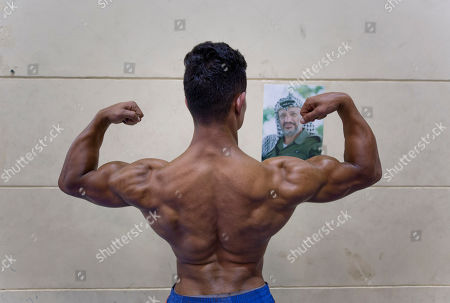 A Palestinian bodybuilder prepares himself during the competitions of the Palestine Bodybuilding Championship 2019, in the West Bank city of Ramallah, Wednesday, Sept. 25. 2019, in front of a photo of the late Palestinian leader Yasser Arafat