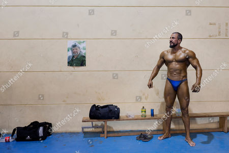 Stock Photo of A Palestinian bodybuilder prepares himself during the competitions of the Palestine Bodybuilding Championship 2019, in the West Bank city of Ramallah, Wednesday, Sept. 25. 2019, in front of a photo of the late Palestinian leader Yasser Arafat