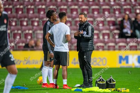Aberdeen manager Derek McInnes (right) speaks with Greg Leigh (#3) of Aberdeen FC and Shay Logan (#2) of Aberdeen FC (white t-shirt) during the warm up before the Betfred Scottish Football League Cup quarter final match between Heart of Midlothian FC and Aberdeen FC at Tynecastle Stadium, Edinburgh