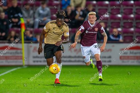 Stock Image of Greg Leigh (#3) of Aberdeen FC and Callumn Morrison (#38) of Heart of Midlothian FC chase a ball during the Betfred Scottish Football League Cup quarter final match between Heart of Midlothian FC and Aberdeen FC at Tynecastle Stadium, Edinburgh