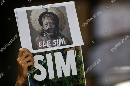 "Stock Image of An activist holds a sign with the image of Brazilian indigenous chief Raoni Metuktire with a phrase written in Portuguese that reads ""Yes Him,"" during a meeting with lawmakers and other organizations in the House of Representatives, in Brasilia, Brazil, . The Kayapo chieftain has called for President Jair Bolsonaro to quit after he downplayed environmental threats in the Amazon rainforest, a day after Bolsonaro attacked Raoni personally during the U.N. General Assembly"