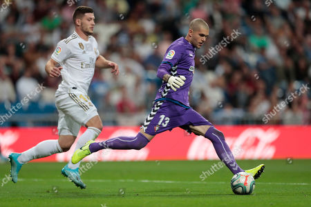 Stock Photo of Osasuna's goalkeeper Ruben Martinez runs for the ball against Real Madrid's Luka Jovic during the Spanish La Liga soccer match between Real Madrid and Osasuna at the Santiago Bernabeu stadium in Madrid, Spain