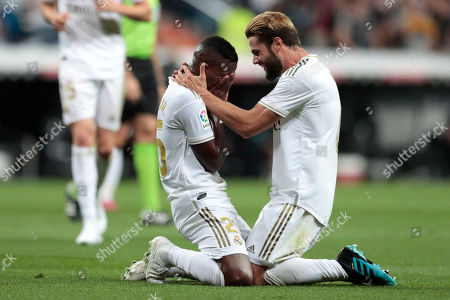 Real Madrid's Vinicius Jr., left, celebrates with teammate Toni Kroos, scoring the opening goal during the Spanish La Liga soccer match between Real Madrid and Osasuna at the Santiago Bernabeu stadium in Madrid, Spain