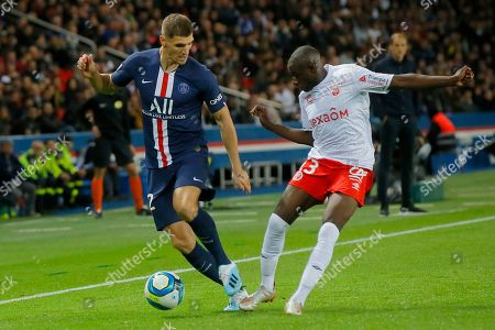 PSG's Thomas Meunier, left, is challenged by Reims' Hassane Kamara during the French League One soccer match between PSG and Reims at the Parc des Princes stadium in Paris