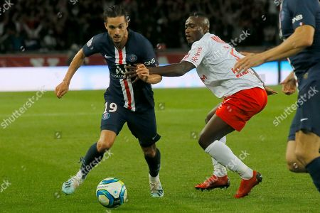 PSG's Pablo Sarabia, left, fights for the ball with Reims' Ghislain Konan during the French League One soccer match between PSG and Reims at the Parc des Princes stadium in Paris