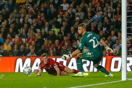 Liverpool midfielder James Milner (7) puts a shot wide past Milton Keynes Dons goalkeeper Stuart Moore (22) during the EFL Cup match between Milton Keynes Dons and Liverpool at stadium:mk, Milton Keynes
