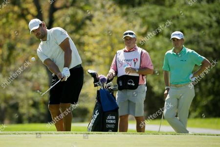 Justin Thomas, Tony Romo. Tony Romo chips the ball onto the third green of the Silverado Resort North Course as Justin Thomas, right, looks on during the pro-am event of the Safeway Open PGA golf tournament, in Napa, Calif