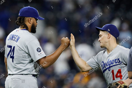Los Angeles Dodgers relief pitcher Kenley Jansen, left, celebrates with teammate second baseman Enrique Hernandez after defeating the San Diego Padres 6-4 in a baseball game, in San Diego