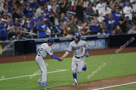 Los Angeles Dodgers' Chris Taylor reacts with third base coach Dino Ebel after hitting a home run during the second inning of a baseball game against the San Diego Padres, in San Diego