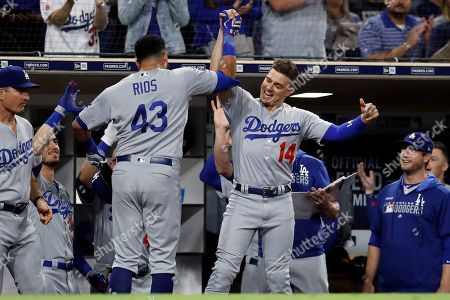 Los Angeles Dodgers' Edwin Rios (43) is greeted by teammate Enrique Hernandez (14) after hitting a home run during the seventh inning of the team's baseball game against the San Diego Padres, in San Diego