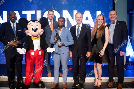 From left, Pierre Thomas with ABC, Mickey Mouse, Rob Connolly with Boys & Girls Club of San Fransisco, Sabrina M., Boys & Girls Clubs of America CEO Jim Clark, Jessica Moore, and Mark Pulley, both with Disney, celebrate with Sabrina, the winner of Boys & Girls Clubs of America's 2019 National Youth of the Year at the annual gala on at the National Building Museum in Washington