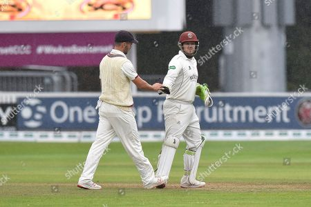 Lewis Gregory of Somerset and Steve Davies of Somerset leave the field as rain stops play during the Specsavers County Champ Div 1 match between Somerset County Cricket Club and Essex County Cricket Club at the Cooper Associates County Ground, Taunton