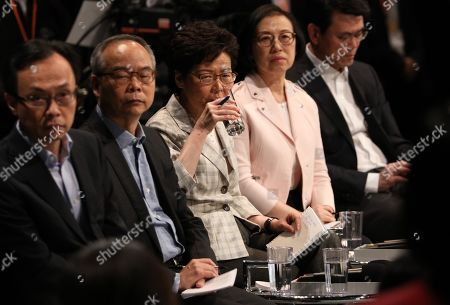 Hong Kong Chief Executive Carrie Lam (C) takes a drink while Patrick Nip (L), Secretary for Constitutional and Mainland Affairs, Lau Kong-wah (2-L), Secretary for Home Affairs of Hong Kong, Sophia Chan (2-R), Secretary for Food and Health, and Edward Yau Tang-wah (R), Secretary for Commerce and Economic looks on as a participant speaks during a meeting with selected participants in Hong Kong, China, 26 September 2019. Lam is holding her first dialogue with the community with a sample of 150 participants selected randomly. Hong Kong has entered its fourth month of mass protests, originally triggered by a now suspended extradition bill to mainland China that have turned into a wider pro-democracy movement.