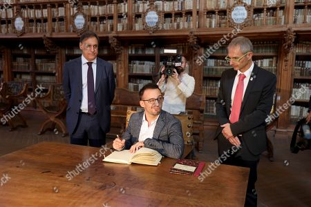 Alejandro Amenabar (C) signs the visitors' book of University of Salamanca, in the framework of the presentation of his film 'Mientras dure la guerra' (While at War) in Salamanca, Castilla y Leon, northern Spain, 26 September 2019. The film opens in Spanish cinemas on 27 September.